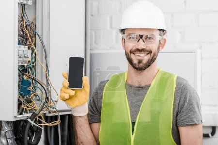 smiling handsome electrician showing smartphone with blank screen near electrical box in corridor