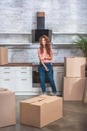 attractive smiling woman with curly hair standing near cardboard boxes at new kitchen