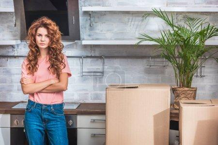 Foto de Mujer atractiva con el pelo rizado de pie con los brazos cruzados cerca de cajas de cartón en nueva cocina y mirando a cámara - Imagen libre de derechos