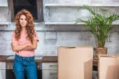 attractive woman with curly hair standing with crossed arms near cardboard boxes at new kitchen and looking at camera