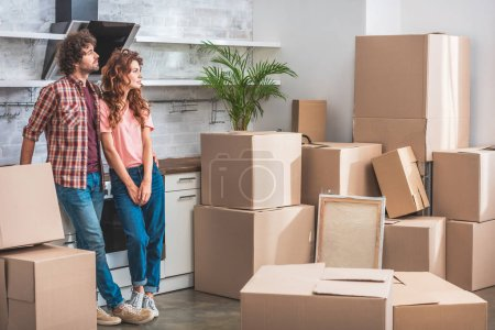 Photo for Girlfriend and boyfriend with curly hair standing near cardboard boxes and looking away at new kitchen - Royalty Free Image