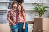smiling couple with curly hair standing near cardboard boxes and looking at camera at new kitchen