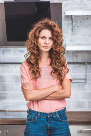 Photo for Beautiful woman with red curly hair standing with crossed arms near cardboard boxes at new kitchen and looking at camera - Royalty Free Image