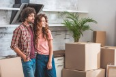couple with curly hair standing near cardboard boxes and looking away at new kitchen