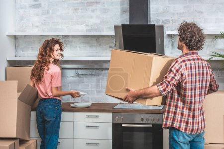 Photo for Boyfriend and girlfriend with curly hair unpacking cardboard boxes together at new kitchen - Royalty Free Image