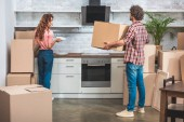boyfriend and girlfriend unpacking utensil from cardboard boxes together at new kitchen