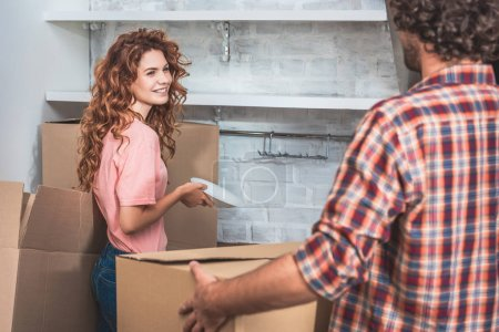 Photo for Boyfriend and smiling girlfriend unpacking cardboard boxes together at new kitchen - Royalty Free Image