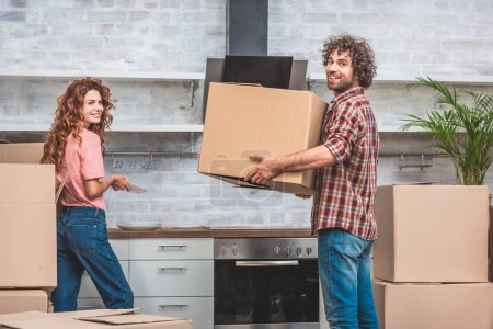 Photo for Happy couple unpacking cardboard boxes together at new kitchen and looking at camera - Royalty Free Image