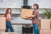 happy couple unpacking cardboard boxes together at new kitchen and looking at camera