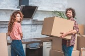 smiling couple unpacking cardboard boxes together at new kitchen and looking at camera