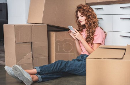 Photo for Attractive woman with curly hair sitting on floor near cardboard boxes and using smartphone at new home - Royalty Free Image