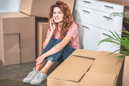 Photo for Smiling attractive woman sitting on floor near cardboard boxes and talking by smartphone at new home - Royalty Free Image
