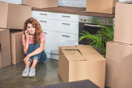 sad woman in casual clothes sitting on floor near cardboard boxes and talking by smartphone at new home