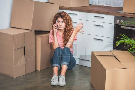 irritated woman with curly hair sitting on floor near cardboard boxes, talking by smartphone and gesturing at new kitchen