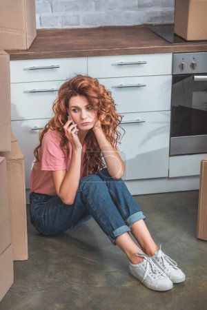 upset attractive woman with curly hair sitting on floor near cardboard boxes and talking by smartphone at new home