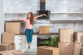 smiling attractive woman with curly hair sitting on kitchen counter between cardboard boxes with outstretched hands at new home