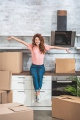 happy beautiful woman sitting on kitchen counter with outstretched hands between cardboard boxes at new home
