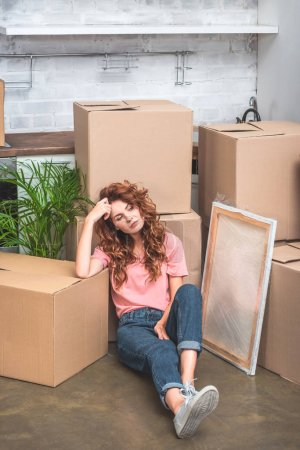 Photo for High angle view of attractive woman with curly red hair sitting on floor near cardboard boxes at new home - Royalty Free Image