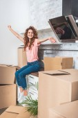 happy attractive woman with curly hair sitting on kitchen counter with outstretched hands between cardboard boxes at new home