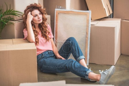 Photo for Attractive woman with curly red hair in casual clothes sitting on floor near cardboard boxes at new home - Royalty Free Image