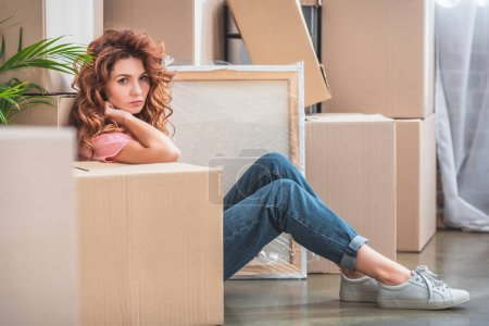 Photo for Attractive woman with curly red hair sitting on floor near cardboard boxes at new home and looking at camera - Royalty Free Image