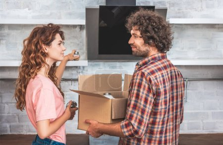 Photo for Side view of couple taking utensil from cardboard box at new home and looking at each other - Royalty Free Image
