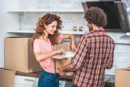 Photo pour Ustensile de prise de couple de boîte en carton à la nouvelle cuisine - image libre de droit