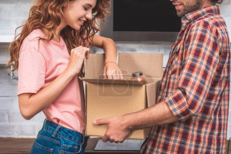 Photo for Cropped image of couple unpacking cardboard box at new home - Royalty Free Image