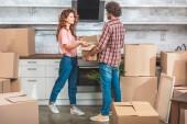 vue latérale du couple déballage ustensile de boîte en carton à la nouvelle cuisine et l'autre en regardant