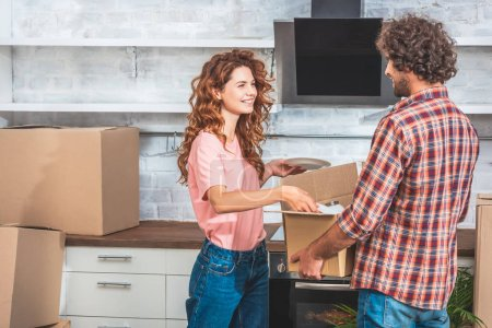 Photo for Smiling couple unpacking utensil from cardboard box at new kitchen and looking at each other - Royalty Free Image