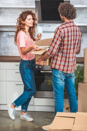 couple unpacking utensil from cardboard box at new kitchen and looking at each other