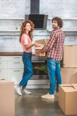 smiling couple unpacking cardboard box together at new home and looking at camera