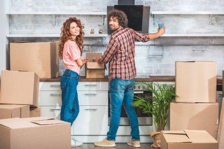 Photo pour Boîtes en carton déballage de couple à la nouvelle cuisine en souriant et regardant la caméra - image libre de droit