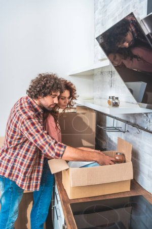 Photo for Side view of couple hugging and unpacking cardboard box in new kitchen - Royalty Free Image