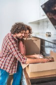 smiling couple hugging and unpacking cardboard box in new kitchen, girlfriend holding salt maid