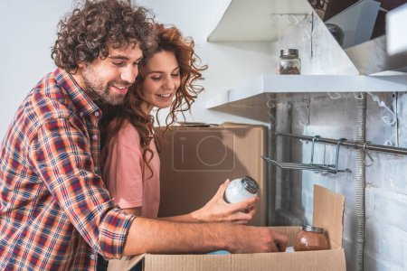 Photo for Smiling couple unpacking cardboard boxes at new home, girlfriend holding salt maid - Royalty Free Image