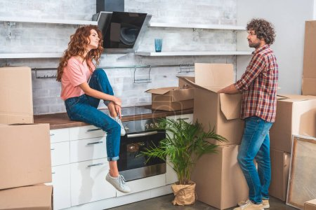 Photo for Side view of couple unpacking cardboard boxes at new home and looking at each other - Royalty Free Image