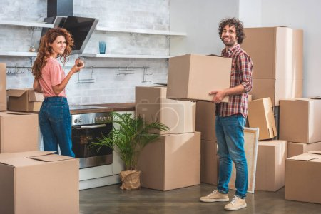 Photo for Smiling couple unpacking cardboard boxes at new kitchen and looking at camera - Royalty Free Image