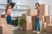 smiling couple unpacking cardboard boxes at new kitchen and looking at camera