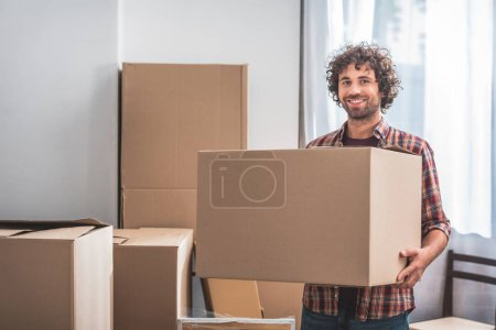 Photo for Smiling handsome man with curly hair holding cardboard box at new home - Royalty Free Image