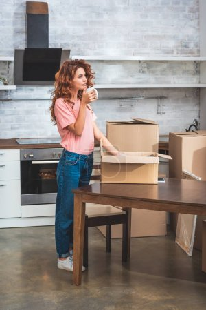 Photo for Beautiful woman drinking coffee and unpacking cardboard box at new home - Royalty Free Image
