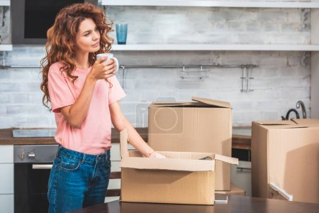 Photo for Attractive woman holding cup of tea and unpacking cardboard box at new home - Royalty Free Image