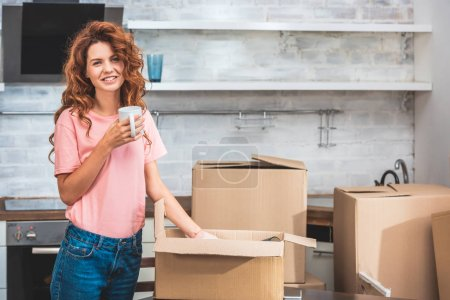 Photo for Smiling beautiful woman holding cup of coffee and unpacking cardboard box at new home - Royalty Free Image