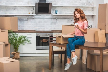 Photo for Beautiful woman holding cup of coffee and unpacking cardboard box on table at new home - Royalty Free Image