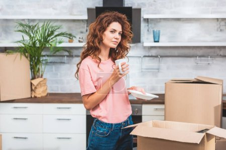 beautiful woman with curly red hair holding cup of coffee and plate at new home