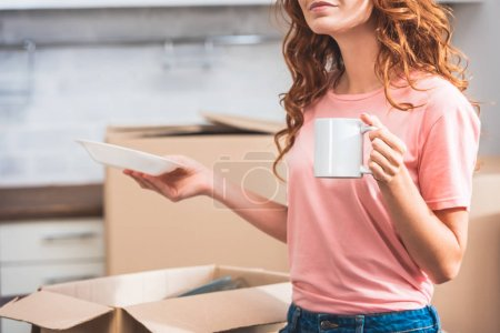 cropped image of woman with curly red hair holding cup of coffee and plate at new home