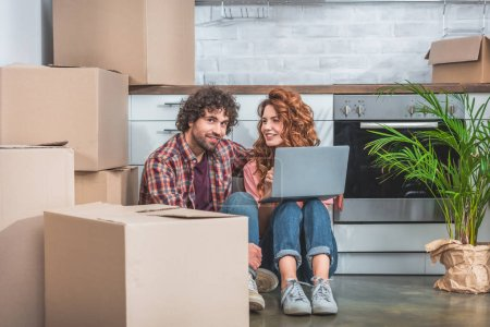 Photo for Smiling couple sitting with laptop near cardboard boxes on floor in new kitchen - Royalty Free Image