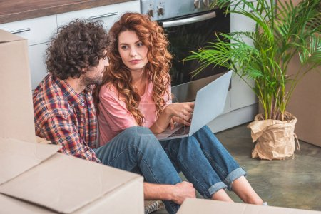 Photo for Couple sitting with laptop near cardboard boxes on floor in new kitchen and looking at each other - Royalty Free Image
