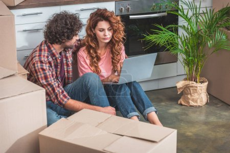 couple with curly hair sitting with laptop near cardboard boxes on floor in new kitchen