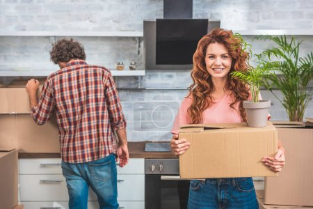 Photo for Couple unpacking cardboard boxes at new home, girlfriend holding box with plant and looking at camera - Royalty Free Image